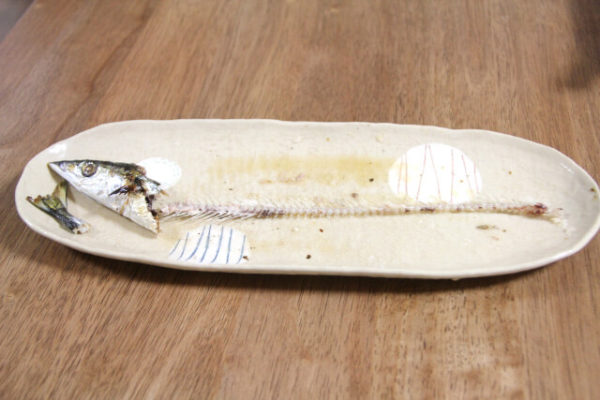 焼き魚を上手に箸で食べるパキスタン人